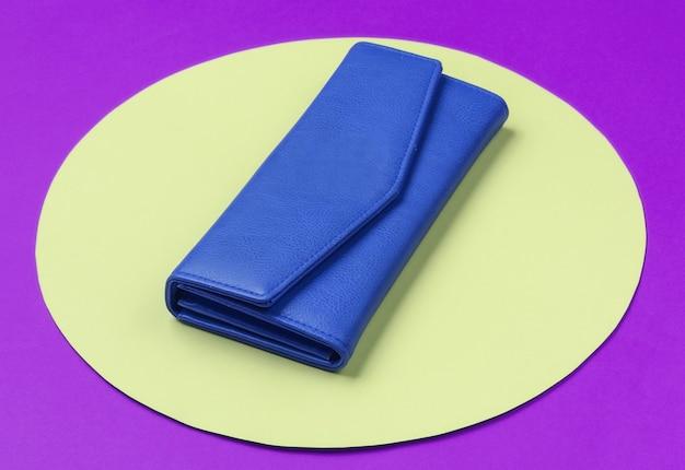 노란색 파스텔 원이 있는 보라색 배경에 세련된 여성용 파란색 가죽 지갑. 창조적 인 최소한의 패션 정물