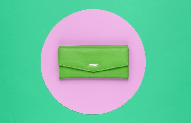 Stylish women's green leather wallet on green background with pink pastel circle. creative minimalistic fashion still life. top view