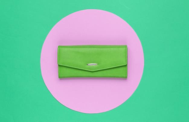분홍색 파스텔 원이 있는 녹색 배경에 세련된 여성용 녹색 가죽 지갑. 창조적 인 최소한의 패션 정물. 평면도