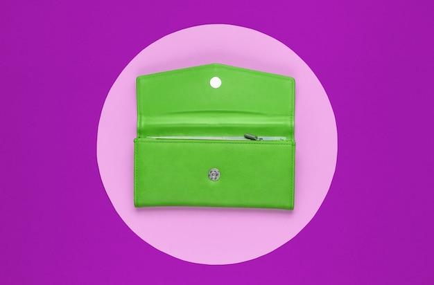 분홍색 파스텔 원이 있는 보라색 배경에 세련된 여성용 녹색 가죽 지갑. 창조적 인 최소한의 패션 정물. 평면도