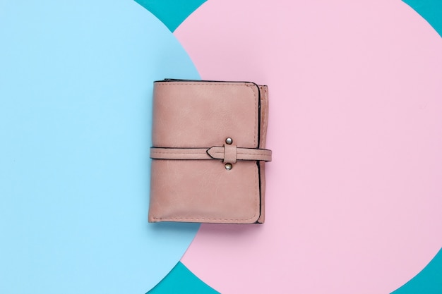 Stylish women's leather wallet on background with blue pink pastel circle. creative minimalistic fashion still life. top view