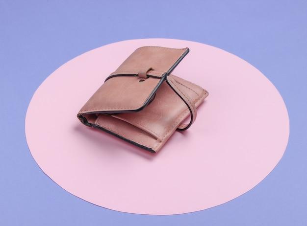 ピンクのパステルサークルと紫の背景にスタイリッシュな女性の革の財布。クリエイティブなミニマルなファッションの静物