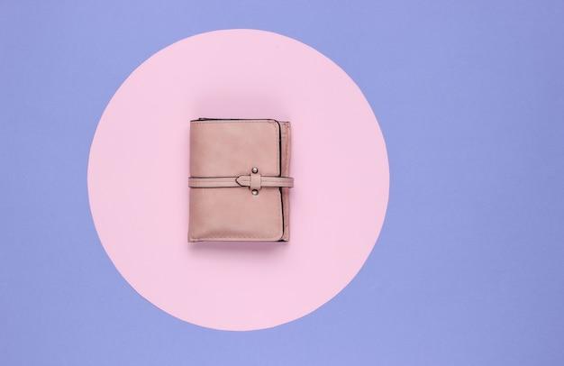 Стильный женский кожаный кошелек на фиолетовом фоне с розовым пастельным кружком. творческий минималистичный модный натюрморт