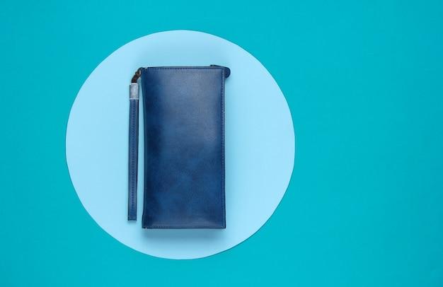 青いパステルサークルで背景にスタイリッシュな女性の革の財布。クリエイティブなミニマルなファッションの静物。上面図