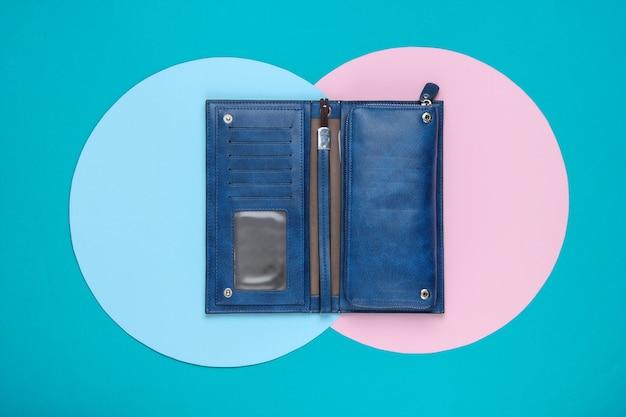 ブルーピンクのパステルサークルを背景にスタイリッシュな女性の革の財布。クリエイティブなミニマルなファッションの静物。上面図