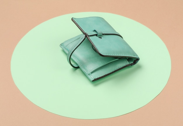 녹색 파스텔 원이 있는 주황색 배경의 세련된 여성용 가죽 지갑. 창조적 인 최소한의 패션 정물