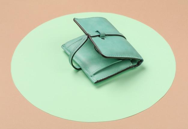 Stylish women's leather wallet on orange background with green pastel circle. creative minimalistic fashion still life