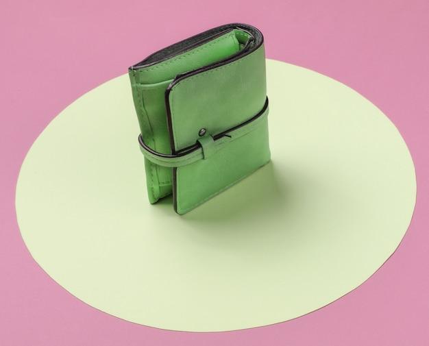 Stylish women's leather wallet on pink background with yellow pastel circle. creative minimalistic fashion still life