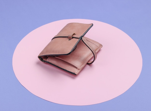 Stylish women's leather wallet on a purple background with a pink pastel circle. creative minimalistic fashion still life