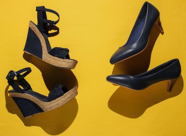 Stylish women's platform sandals, high heel shoes on yellow paper