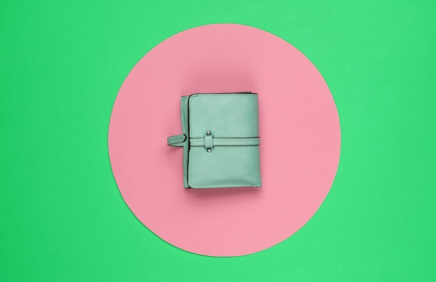 Stylish women's red leather wallet on green background with pink pastel circle. creative minimalistic fashion still life. top view