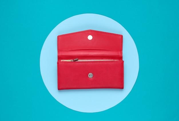 青いパステルサークルで背景にスタイリッシュな女性の赤い革の財布。クリエイティブなミニマルなファッションの静物。上面図