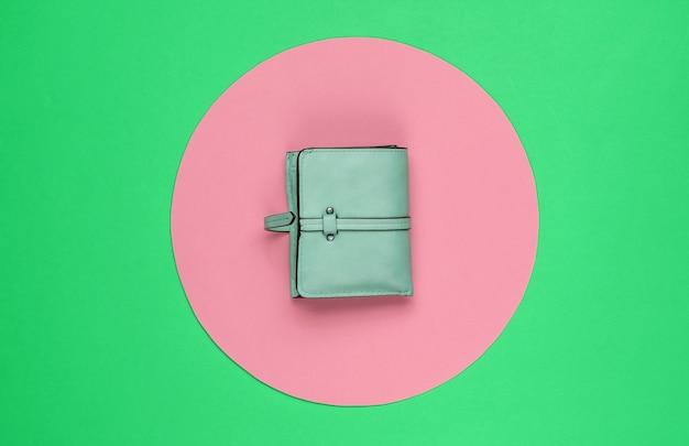 분홍색 파스텔 원이 있는 녹색 배경에 세련된 여성용 빨간색 가죽 지갑. 창조적 인 최소한의 패션 정물. 평면도