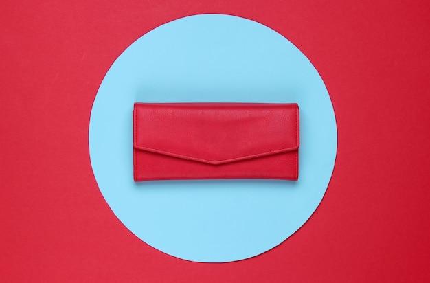Стильный женский красный кожаный кошелек на красном фоне с голубым пастельным кругом. творческий минималистичный модный натюрморт. вид сверху