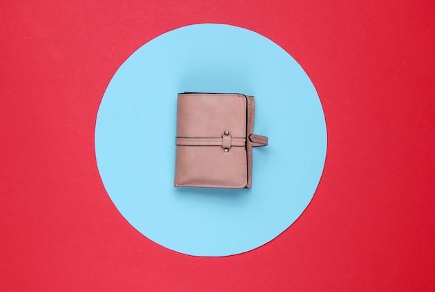 青いパステルサークルと赤の背景にスタイリッシュな女性の赤い革の財布。クリエイティブなミニマルなファッションの静物。上面図
