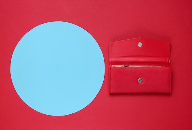 コピースペースのための青いパステルサークルと赤い背景のスタイリッシュな女性の赤い革の財布。クリエイティブなミニマルなファッションの静物。上面図