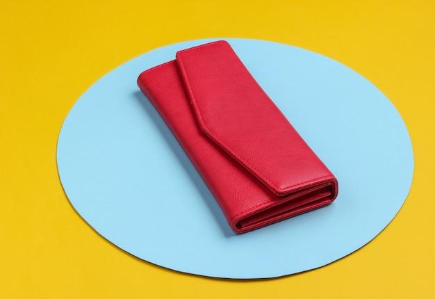 青いパステルサークルと黄色の背景にスタイリッシュな女性の赤い革の財布。クリエイティブなミニマルなファッションの静物