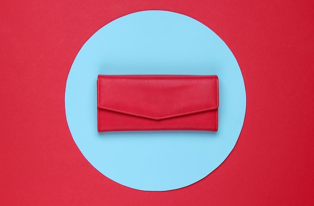 Stylish women's red leather wallet on red background with blue pastel circle. creative minimalistic fashion still life. top view