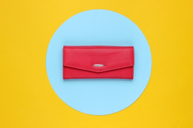 Stylish women's red leather wallet on yellow background with blue pastel circle. creative minimalistic fashion still life. top view