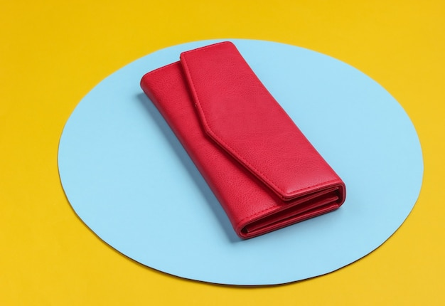 Stylish women's red leather wallet on yellow background with blue pastel circle. creative minimalistic fashion still life
