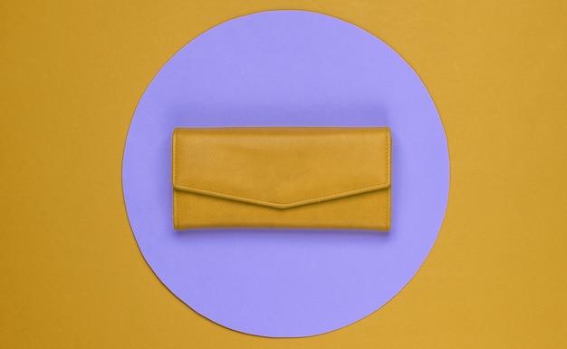 보라색 파스텔 원이 있는 주황색 배경의 세련된 여성용 노란색 가죽 지갑. 창조적 인 최소한의 패션 정물. 평면도