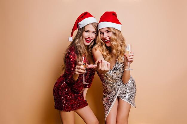 Donne alla moda in cappelli di babbo natale che celebrano insieme il nuovo anno