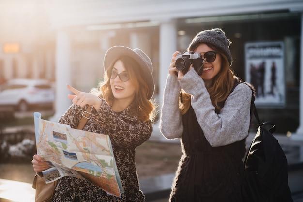 寒い日に屋外で時間を過ごし、カメラで新しい場所を探索するスタイリッシュな女性。ゴージャスな女性写真家が妹と一緒に街を歩き、指先で指をさして笑顔を持って地図を持ちます。