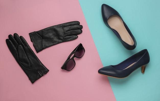 ピンクブルーのパステルカラーの背景にスタイリッシュなレディースアクセサリーと靴レザーハイヒールの靴手袋サングラス上面図