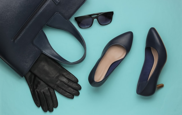 Stylish womens accessories and shoes on a blue pastel background leather high heel shoes bag sunglasses gloves top view
