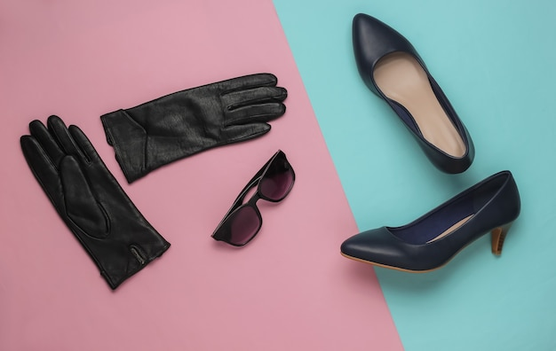 Stylish womens accessories and shoes on pink blue pastel background leather high heel shoes gloves sunglassess top view