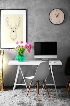 Stylish working place with computer and wooden table.