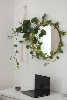 Стильное рабочее место дома с ноутбуком на столе и круглым зеркалом с растением над ним