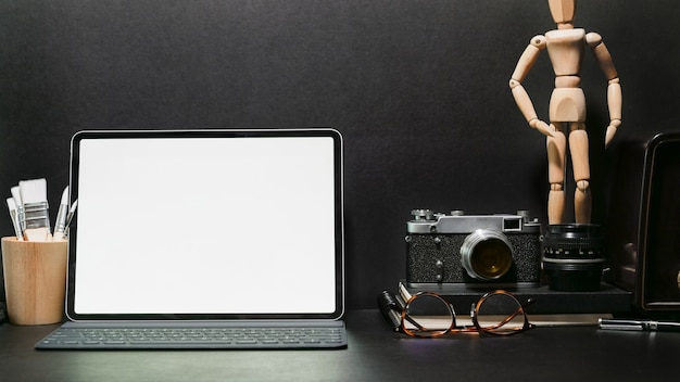 Stylish workplace desk vintage camera, blank screen tablet and gadget on dark leather table