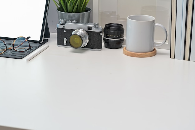 Stylish workplace desk vintage camera, blank screen tablet and gadget