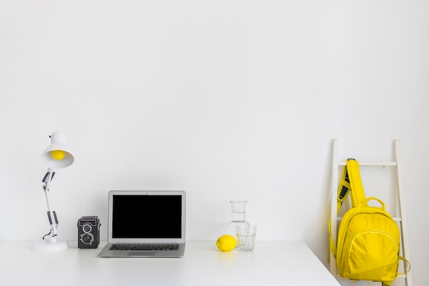 Stylish workplace in white and yellow colors with backpack and laptop
