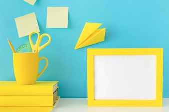 Stylish workplace with yellow photo frame and paper plane