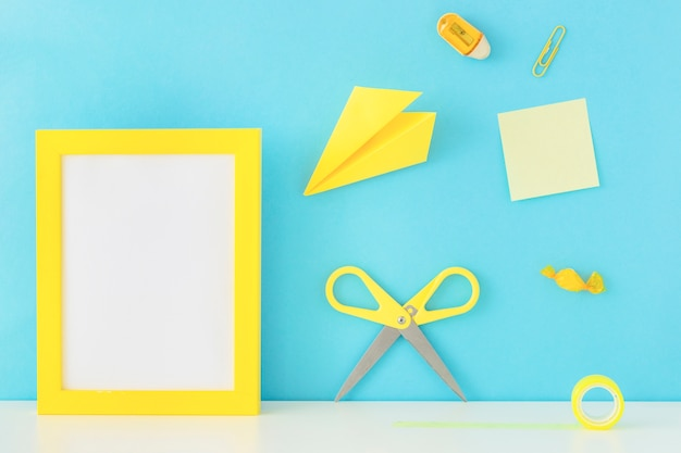 Stylish workplace with yellow photo frame and writing accessories