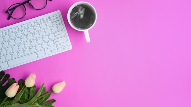 보라색 배경에 세련된 작업 공간 커피 컵, 꽃, 노트북 및 키보드.