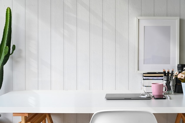 Stylish workspace laptop, poster, home office supplies and copy space.