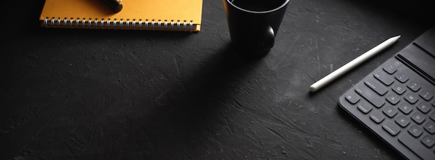 Stylish workspace with coffee cup, notebook, stylus, digital tablet on black table