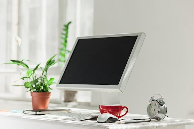 自宅またはスタジオにコンピューターがあるスタイリッシュなワークスペース