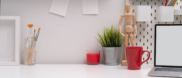 Stylish workspace with copy space, mock-up laptop, mug, painting brushes and decorations