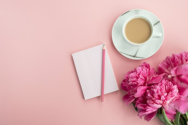Stylish workspace with cup coffee,notepad and pink peony flowers. woman working table