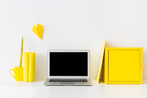 Stylish workspace with laptop and yellow metal box