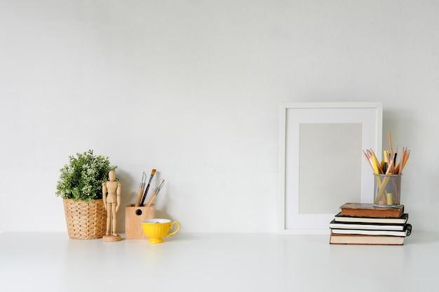 포스터, 책 및 가제트가있는 세련된 작업 공간. 직장 책상 및 복사 공간.