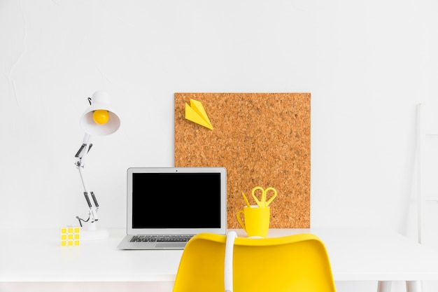 Stylish workspace in yellow and white colors with cork board