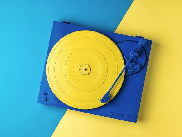 노란색과 파란색 배경에 세련 된 노란색과 파란색 비닐 레코드 플레이어. 복고풍 음악 장비.