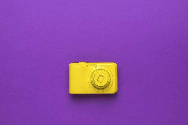보라색 배경에 세련된 노란색 복고풍 카메라입니다. 플랫 레이.