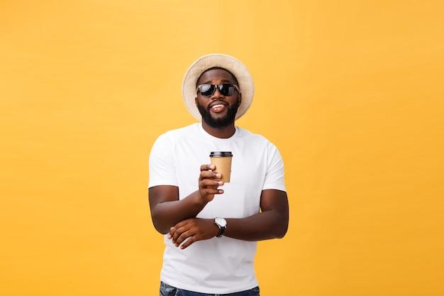 分離されたテイクアウトコーヒーのカップを保持しているスタイリッシュな若いアフリカ系アメリカ人の男