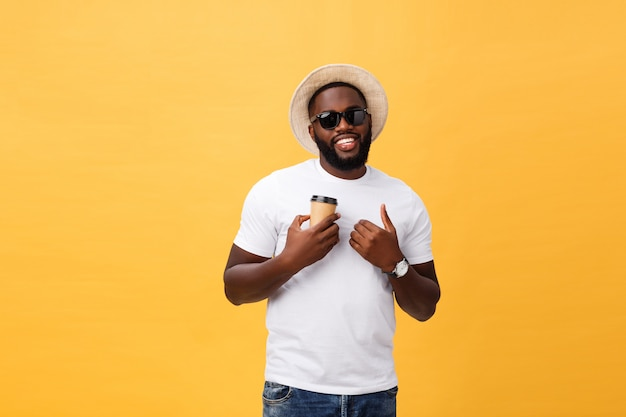 Stylish young african american man holding cup of take away coffee isolated over yellow background.